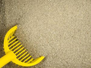 Feines Katzenstreu mit gelber Schaufel